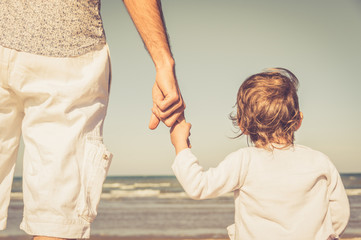 Father's hand lead his child son in summer beach nature outdoor, trust family concept