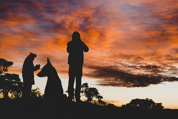 Men and dog silhouettes at sunrise in Brazil