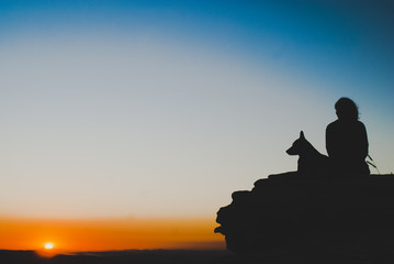 Girl and dog silhouettes at sunrise in Brazil