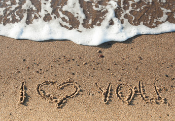 """Words """"I Love You"""" written on sand with white foam on background"""