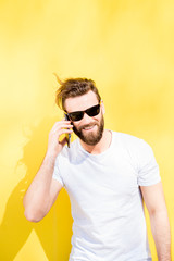 Colorful portrait of a handsome man dressed in white t-shirt talking with phone on the yellow background