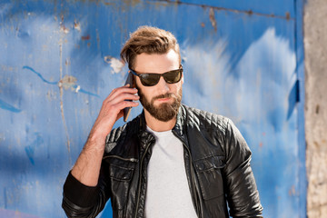 Handsome bearded man talking with phone on the blue wall background
