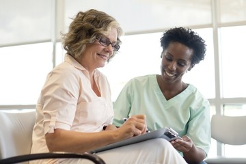 Woman filling out form with nurse