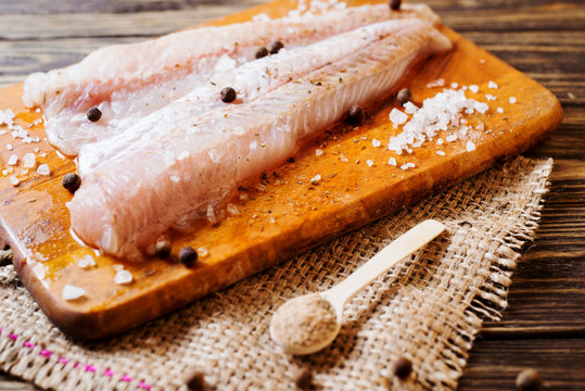 Fresh raw fish, fillet of hake with spices, black pepper and salt on a wooden board, background