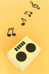 Musical background. Notes and radio cut out from a cardboard on a yellow fabric. Funny background. music concept.