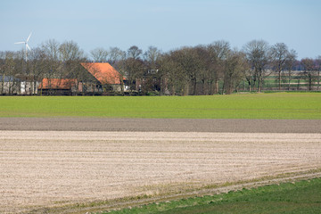 Typical Dutch polder landscape with farmhouse and bare fields