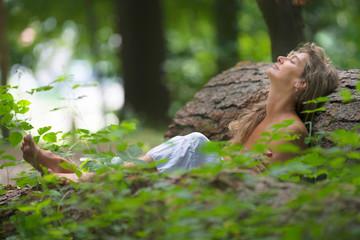 Erschöpfte Frau im Wald entspannt an Baumstamm angelehnt
