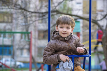 adorable little boy swinging in the park