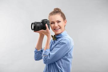 Beautiful female tourist with camera on light background
