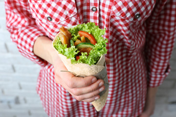 Woman holding delicious kebab roll, closeup