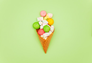 photo of colorful marshmallows and waffle cone on the wonderful green background