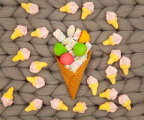 photo of colorful marshmallows and waffle cone on the wonderful grey blanket background