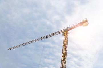 Crane against the blue cloudy sky.