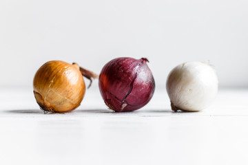 Three bulbs on a white wooden background. White onions, onions and red onions