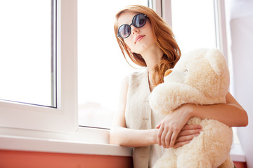 photo of beautiful young woman hugging teddy bear and standing near the window