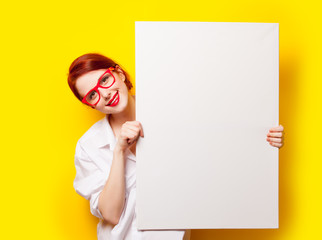 photo of beautiful young woman holding empty poster on the wonderful yellow studio background