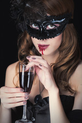 photo of beautiful young woman in vampire character with glass of wine