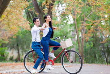 photo of cute couple sitting on bicycle and holding hands on the wonderful autumn park background