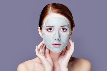 photo of beautiful young woman with mask on her face on the wonderful grey background