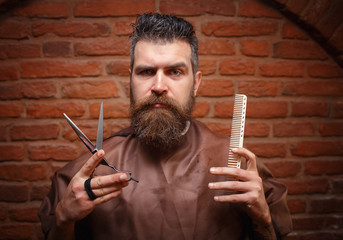 Brutal bearded man with a beautiful mustache in a barber shop against a brick wall holding a pair of scissors and a comb