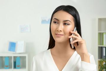 Beautiful Asian woman talking on phone in office