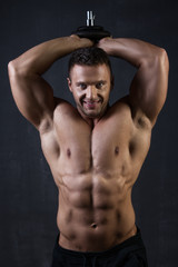 Handsome muscular bodybuilder showing his muscles.