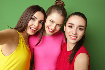 Funny young women taking selfie on color background