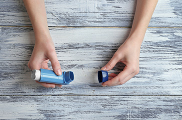 Female hands holding asthma inhaler on wooden background