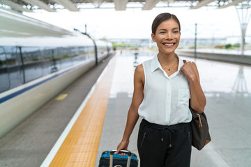 Businesswoman at train station arriving at destination leaving vehicle with hand luggage. Happy Asian woman on commute to work in city.