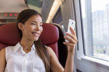 Asian woman using smartphone app taking pictures of the view while traveling in train. Happy young lady watching video holding mobile phone during transport on travel vacation.