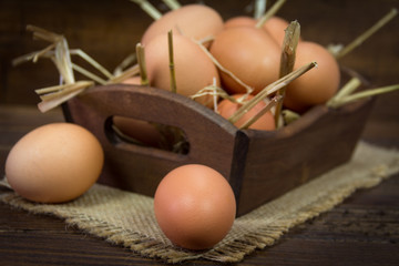Chicken eggs with straw in wooden bowl on wooden background