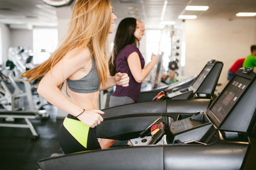 young woman is engaged fitness in gym. Performs cardio load on treadmill, running and walking with acceleration. sport, fit, lifestyle, technology and people concept
