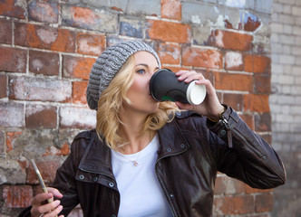 Young woman standing in front of brick wall drinking coffee to go and using mobile phone