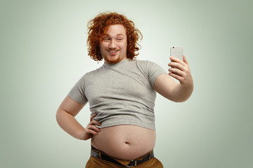 Obese young male with curly ginger hair and beard holding mobile phone, posing for selfie, looking at camera with flirty smile while his fat belly hanging out of grey shrunk t-shirt and jeans pants
