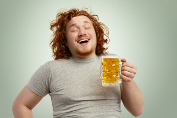 Funny young Caucasian male feeling happy and relaxed, anticipating fresh cold beer in his hands after hard working day, closing eyes in enjoyment. Bearded overweight redhead man drinking lager