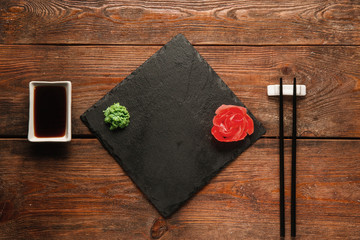 Japanese food background. Empty black slate with ginger and wasabi, chopsticks and soy served on wooden dark rustic table, flat lay, void