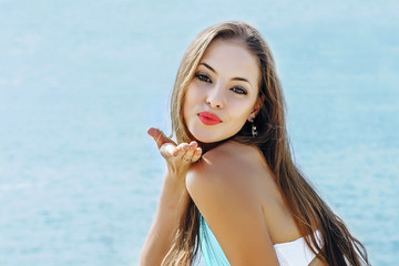 beautiful young girl on the sea send air kiss