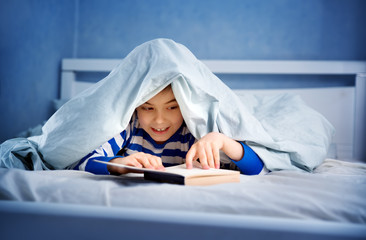 boy lying in bed with a book. child reading
