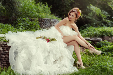 Sexy bride woman with long legs in lush wedding dress sits on nature.