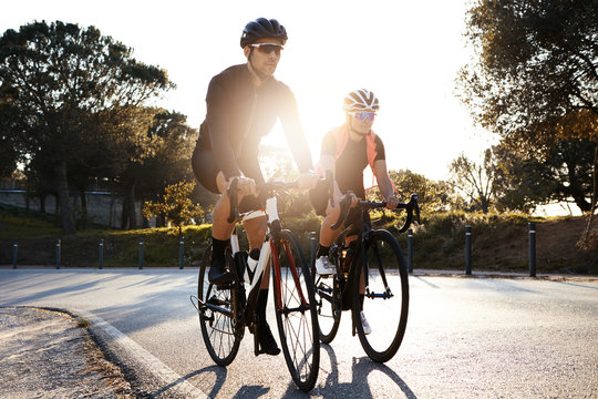 Handsome bearded professional male cyclist riding his racing bicycle in the morning together with his girlfriend, both wearing protective helmets and eyeglasses, sun shining through between them
