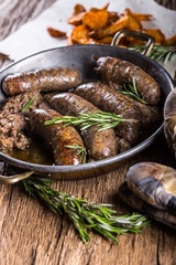 Sausages.Roasted pork sausage in a pan with potatoes and rosemary.