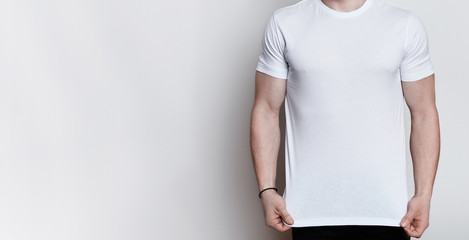 A horizontal portrait of muscular young man wearing white T-shirt posing in a studio over white background with empty space. Mock up template for design print. Athletic body over white.
