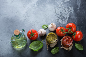 Red and green pesto sauces on a grey stone background, horizontal shot with copyspace
