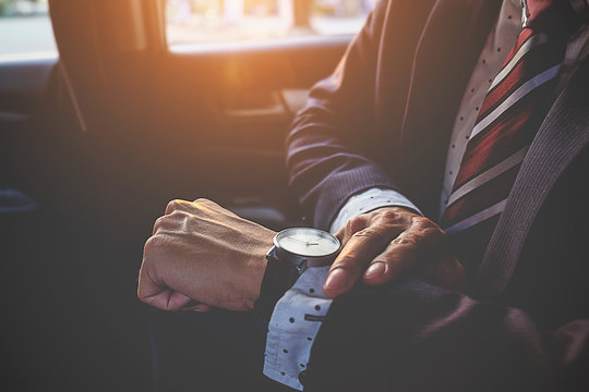 Businessman looking at the time on his wrist watch in car. Business concept.