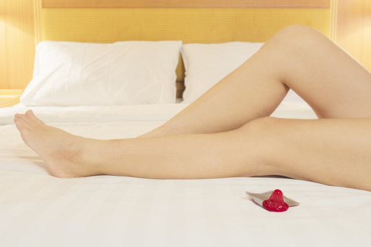 Lady lying on bed showing her leg with red condom on white bed, safe sex concept