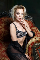 Portrait of a beautiful sexy blond woman in lingerie in a chic vintage chair.
