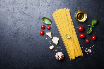 Italian food background with uncooked spaghetti, tomato, basil leaves, cheese, garlic and olive oil on black table top view in flat lay style. Ingredients for cooking pasta with space for recipe.