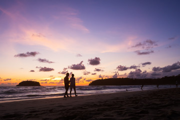 Couple walking on the beach at sunset.