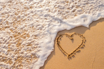 Heart drawn on the beach sand with sea foam and wave.