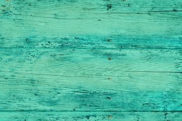 Wood plank fence in green and turquoise colors close up. Detailed background photo texture. Wooden wall abstract background.